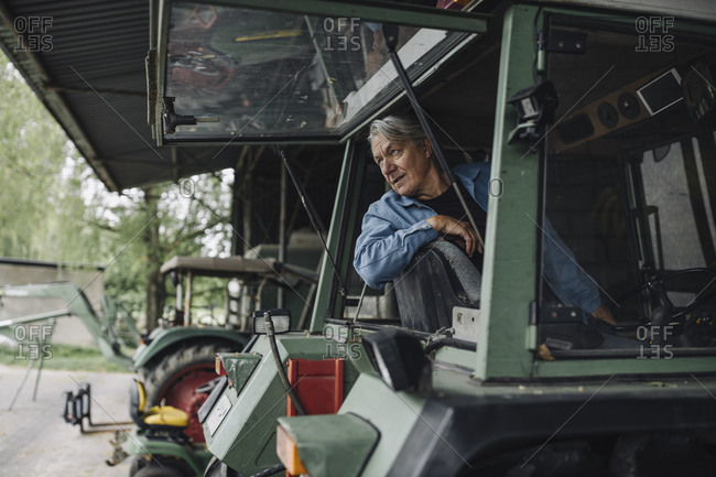 Senior man driving tractor on a farm