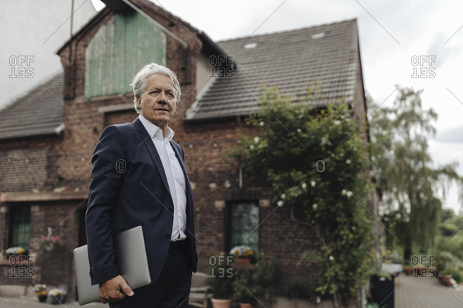 Portrait of a senior businessman holding laptop in front of a farmhouse