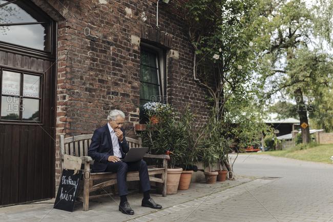 Senior businessman sitting at a farmhouse using laptop