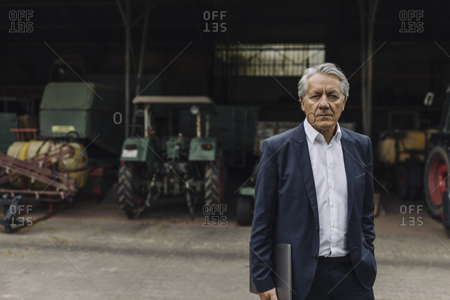 Portrait of a senior businessman on a farm with tractor in barn
