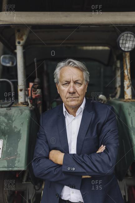 Portrait of a senior businessman at tractor on a farm