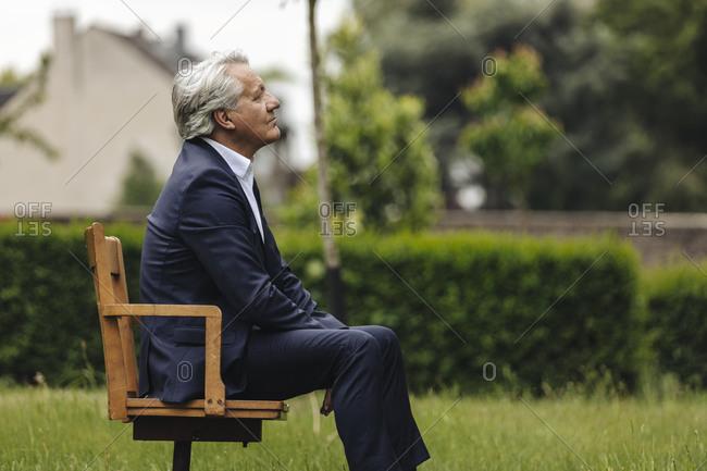 Senior businessman sitting on a chair in a rural garden