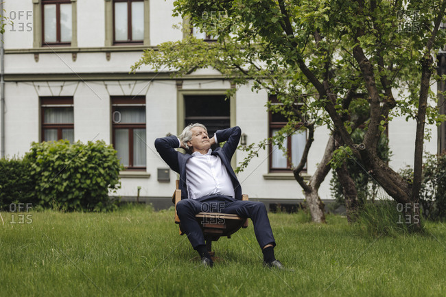 Relaxed senior businessman sitting on a chair in a rural garden looking up
