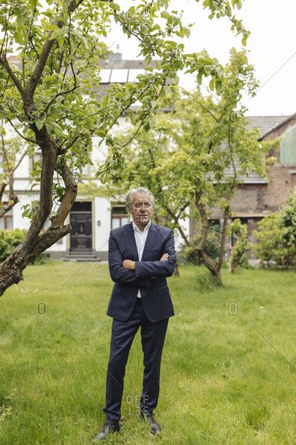 Confident senior businessman standing in a rural garden