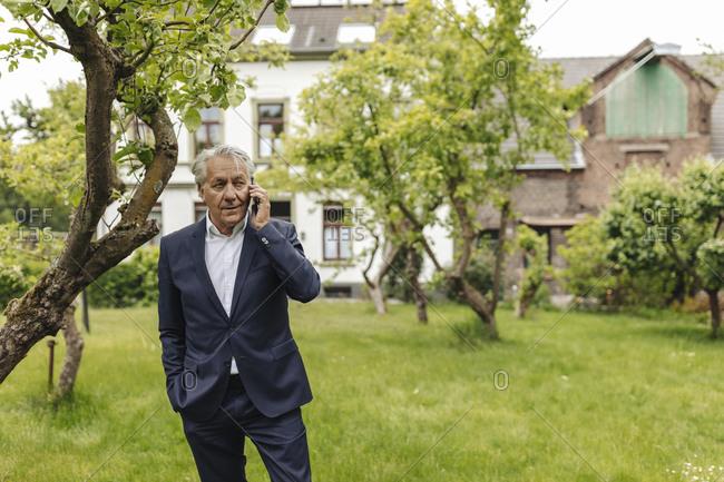 Senior businessman on the phone in a rural garden