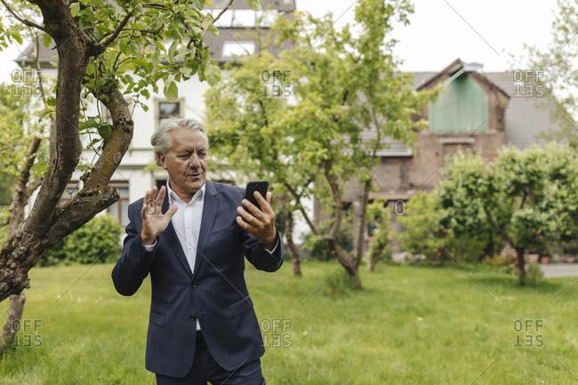 Senior businessman using smartphone in a rural garden
