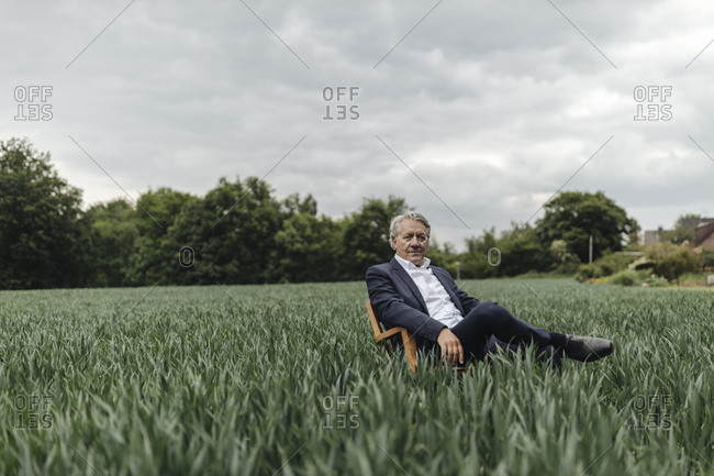 Senior businessman sitting on a chair in a field in the countryside