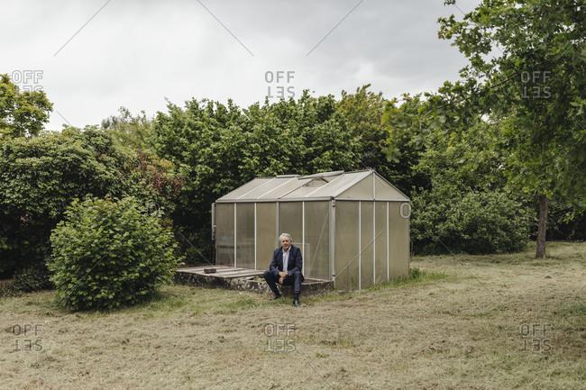 Senior businessman sitting at a greenhouse