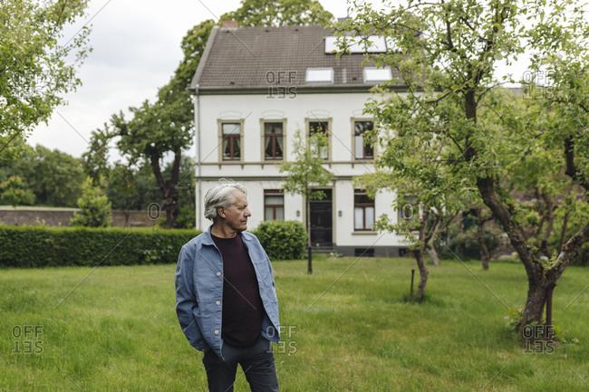 Senior man standing in a rural garden looking around