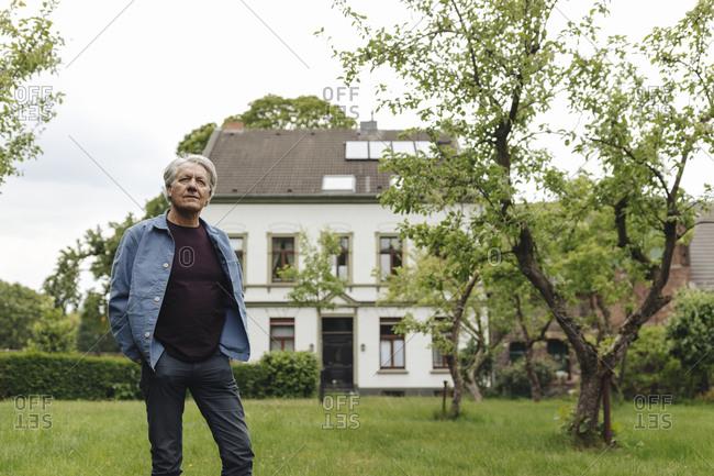 Senior man standing in a rural garden