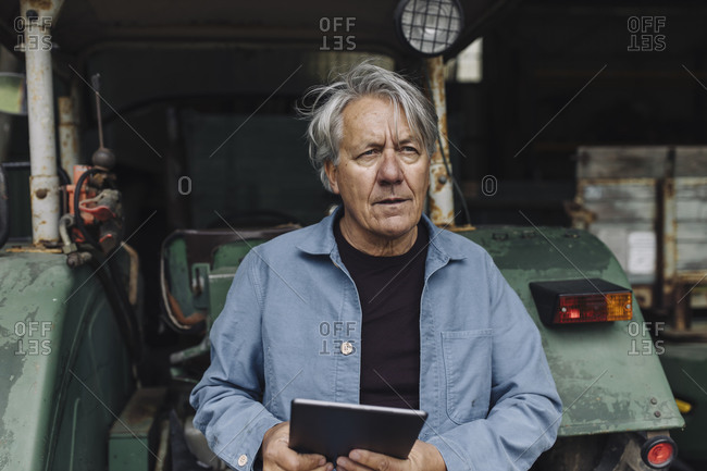 Senior man holding tablet on a farm with tractor in barn