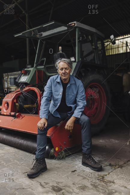 Senior man on a farm sitting on a tractor in barn