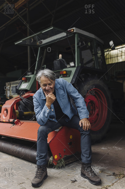 Smiling senior man on a farm sitting on a tractor in barn