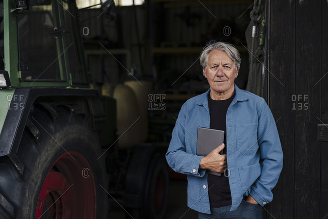 Portrait of a confident senior man holding tablet on a farm with tractor in barn