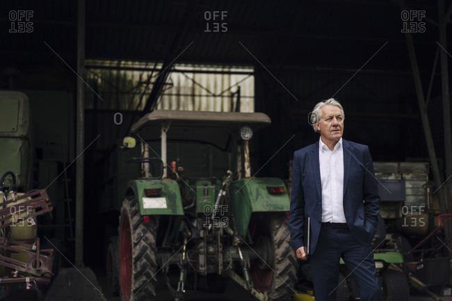 Senior businessman holding laptop on a farm with tractor in barn