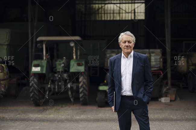Portrait of senior businessman holding laptop on a farm with tractor in barn