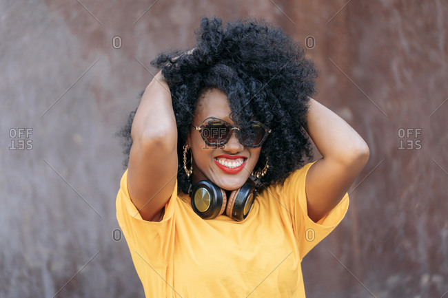 Smiling woman with afro hair and sunglasses and hands in hair
