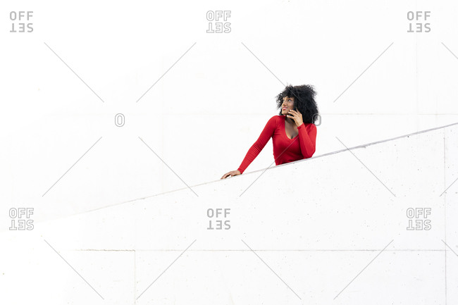 Young woman with afro hair using smartphone on white ramp
