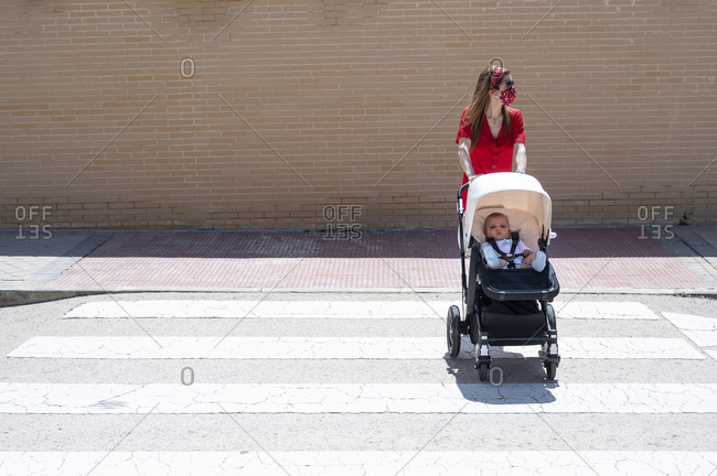 Mother wearing mask pushing son in baby carriage while walking on street