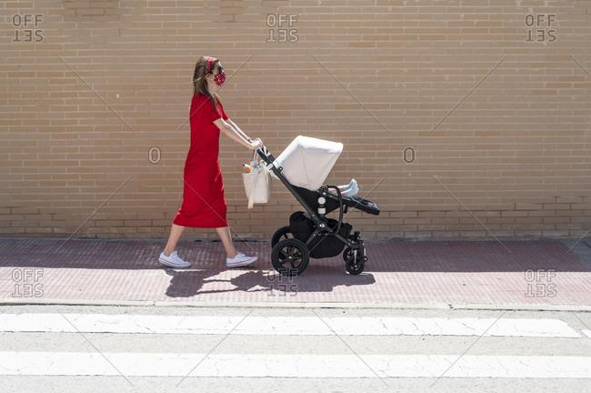 Mother wearing mask pushing son in baby carriage while walking on sidewalk