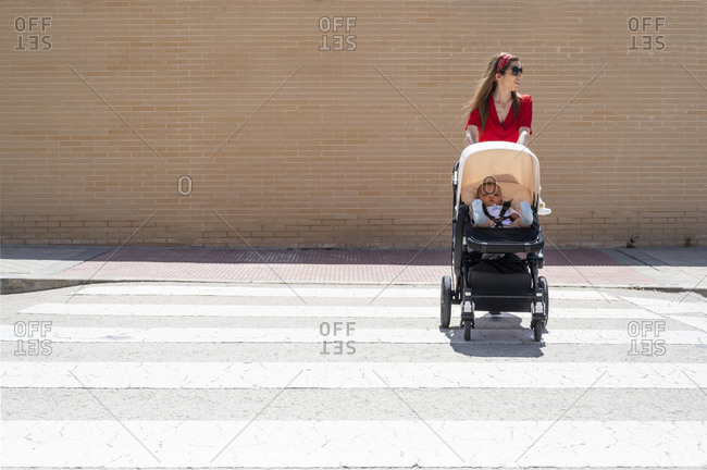Mother wearing sunglasses pushing son in baby carriage while walking on street