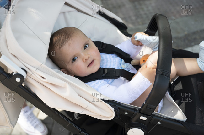 Close-up of cute baby boy lying in carriage