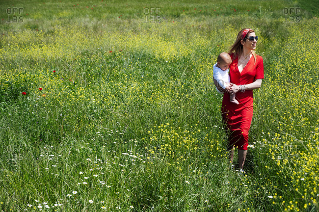 Woman carrying baby son while walking on grassy land during sunny day