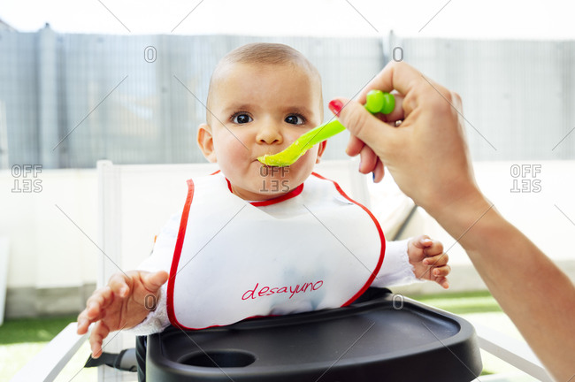 Cropped hand of mother feeding cute son sitting on high chair at home