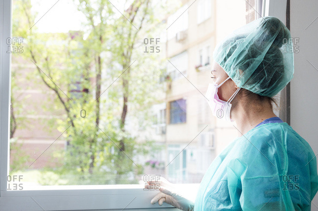 Female nurse wearing protective workwear looking through window in hospital