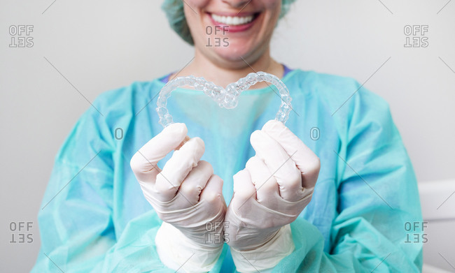 Close-up of nurse holding dental aligners in heart shape at clinic