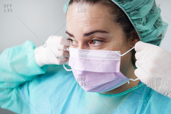 Close-up of nurse wearing surgical mask looking away in clinic