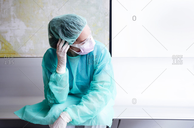Sad doctor wearing protective workwear sitting against wall in hospital