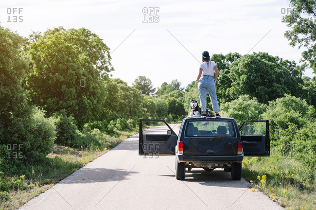Woman standing by dog on vehicle roof against sky during sunny day