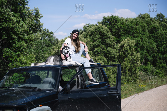 Smiling woman sitting with dog on roof during sunny day