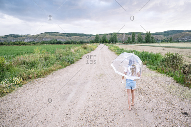 Girl with umbrella walking on dirt road during monsoon