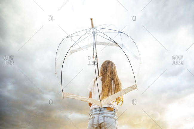 Blond girl holding transparent umbrella during monsoon