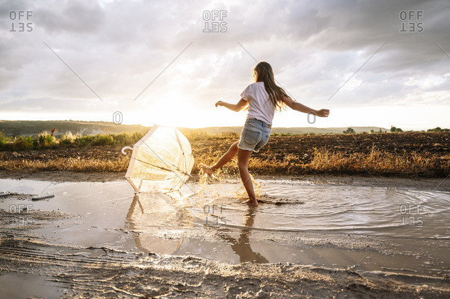 Girl splashing water over umbrella on puddle during sunset