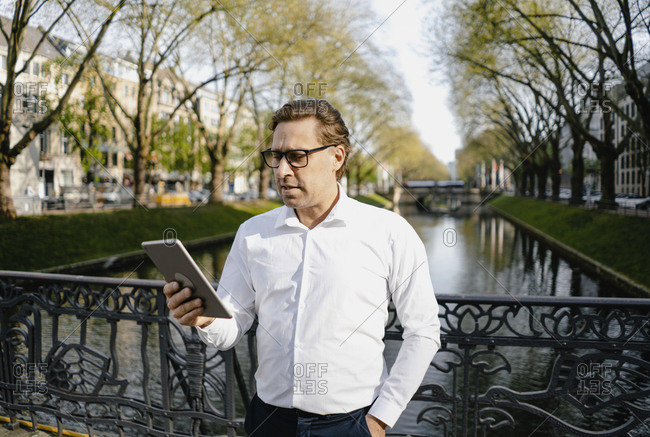 Businessman using tablet at a channel in the city