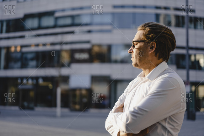 Businessman with closed eyes in sunshine in the city