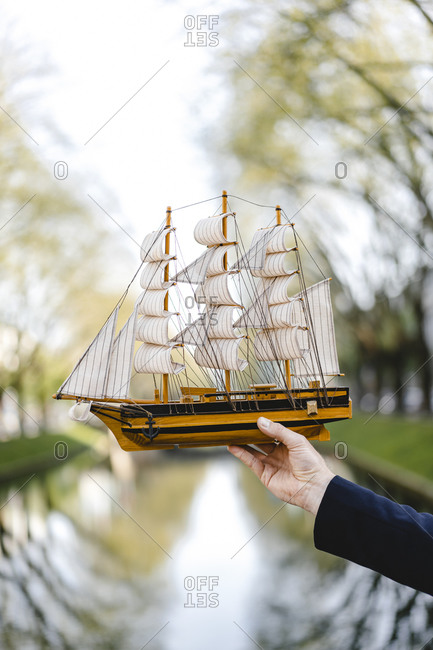 Hand of a man holding model ship at a channel