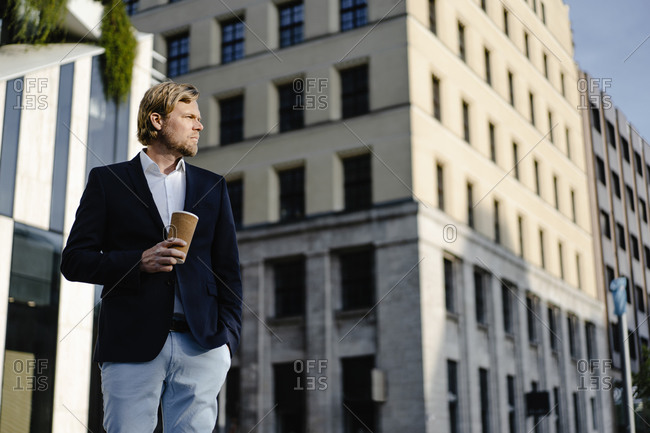 Businessman with takeaway coffee in the city looking around