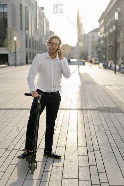 Businessman with kick scooter on the phone in the city