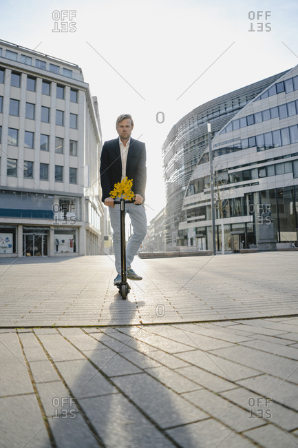 Businessman with kick scooter and bunch of flowers in the city