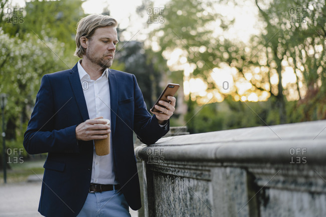 Businessman with takeaway coffee using smartphone in city park