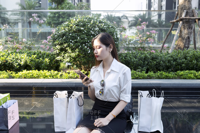 Young woman using smart phone while sitting with shopping bags on seat in city