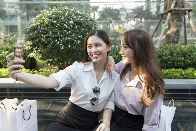 Smiling young woman taking selfie with female friend while sitting on seat in city