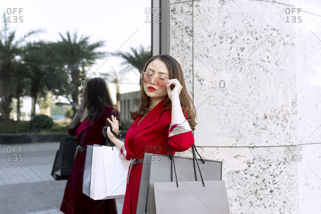 Young woman wearing sunglasses carrying shopping bags while standing by modern building