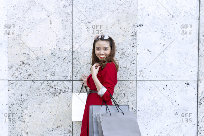 Smiling woman carrying shopping bags while standing by wall