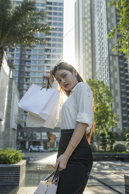 Confident woman holding shopping bags while standing against modern buildings in city
