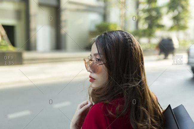 Close-up of young woman wearing sunglasses carrying shopping bag on street in city